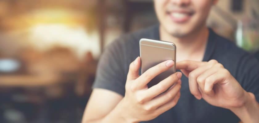 Uśmiechnięty mężczyzna ze smartfonem.
